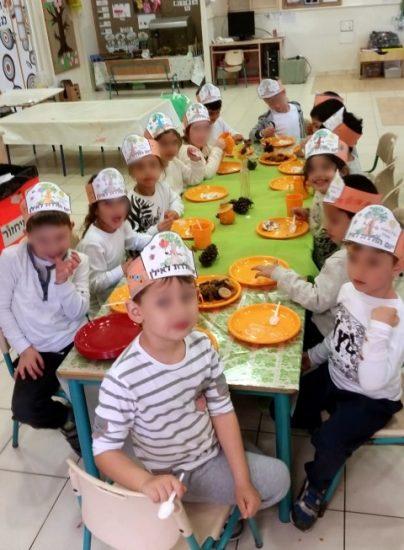 ילדי גן סביב השולחן בטו בשבט
