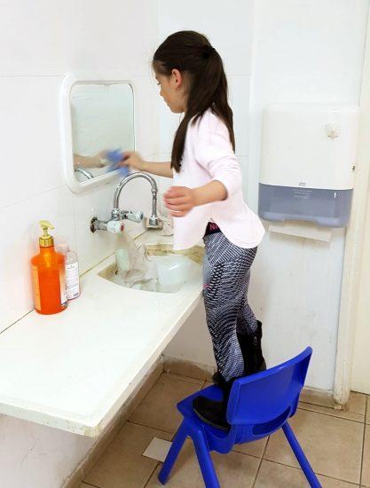ילדה מנקה את המראה