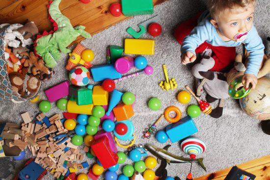 תינוק בחדר מלא צעצועים