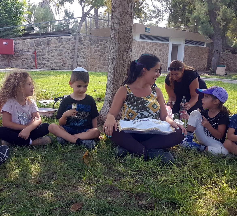 גננת וילדים על הדשא