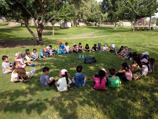 ילדי גן יושבים במעגל בדשא