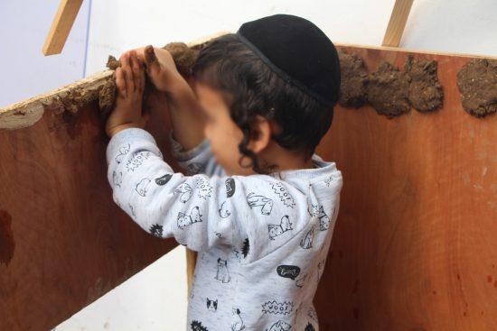 ילד מצפה בית עץ בבוץ