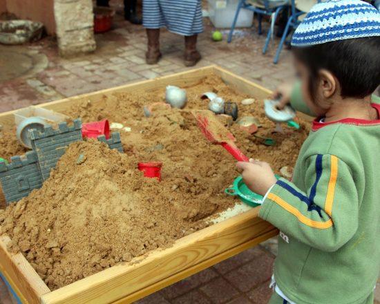 ילד חרדי משחק בשולחן חול