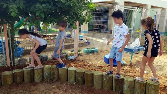 ילדים מדלגים על בולי עץ