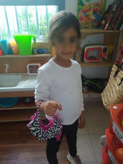 ילדה מחזיקה תיק שארגה בעצמה