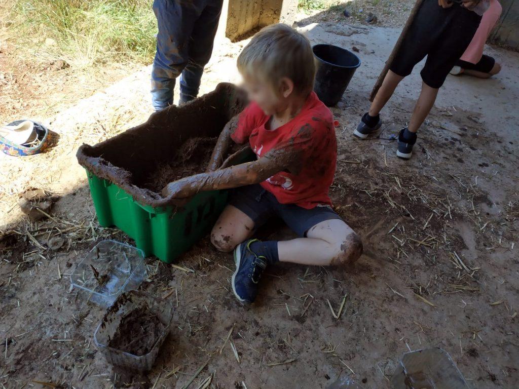 הרשת הירוקה: חינוך חוץ - ילד משחק ליד גיגית בוץ